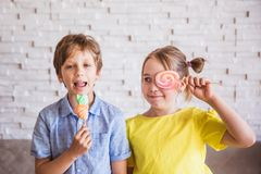 Adorable girl and boy holding colorful sweet meringues on a stick on Easter day royalty free stock photo