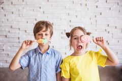 Adorable girl and boy holding colorful sweet meringues on a stick on Easter day stock images