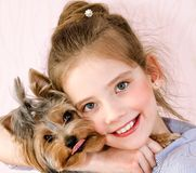 Adorable smiling little girl child holding and playing with puppy yorkshire terrier royalty free stock photography