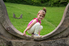 Adorable Smiling Little Girl Crouching On The Stonewall And Looking At The Camera In The Park royalty free stock image