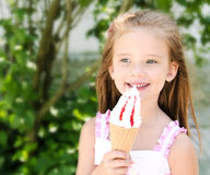 Adorable smiling little girl eating ice cream Stock Images