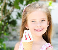 Adorable smiling little girl eating ice cream Royalty Free Stock Images