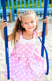 Adorable smiling little girl having fun on a swing Stock Images