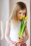 Adorable smiling little girl holding daffodils Stock Photos
