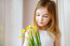 Adorable smiling little girl holding daffodils Royalty Free Stock Image