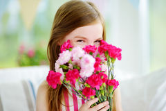 Adorable smiling little girl holding flowers for her mom Stock Image
