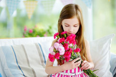 Adorable smiling little girl holding flowers for her mom Stock Photography