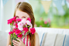 Adorable smiling little girl holding flowers for her mom on mother`s day Stock Photos