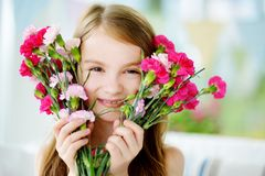 Adorable smiling little girl holding flowers for her mom Stock Photo