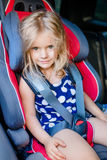 Adorable smiling little girl with long blond hair buckled in car Royalty Free Stock Photo