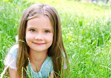 Adorable smiling little girl lying on grass in summer day Stock Images