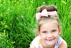 Adorable smiling little girl on the meadow in summer day Royalty Free Stock Photos