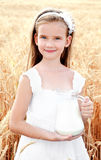 Adorable smiling little girl with milk on field of wheat royalty free stock image