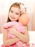 Adorable smiling little girl playing with a doll Royalty Free Stock Photography
