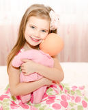 Adorable smiling little girl playing with a doll Stock Images