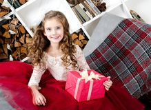 Adorable smiling little girl in princess dress holding gift box