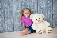 Adorable smiling little girl sitting near a gray wooden wall background and hugging a white teddy bear.  royalty free stock image