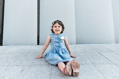 Cute girl smilling near the grey wall. Childhood concept royalty free stock photography