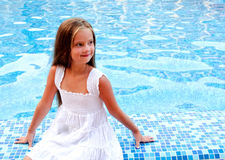 Adorable smiling little girl sitting near the swimming pool stock images