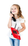 Adorable smiling little girl speaking by phone. Isolated on a white Royalty Free Stock Photography