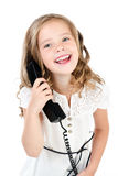 Adorable smiling little girl speaking by phone isolated. On a white Stock Photos