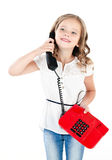 Adorable smiling little girl speaking by phone isolated. On a white Stock Photo