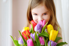 Adorable smiling little girl with tulips Royalty Free Stock Image