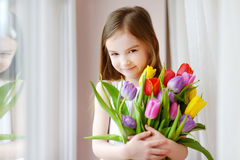 Adorable smiling little girl with tulips Stock Images