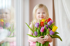 Adorable smiling little girl with tulips Stock Photo