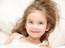 Adorable smiling little girl waked up. In her bed royalty free stock image