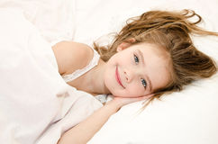 Adorable smiling little girl waked up. In her bed royalty free stock photo