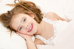 Adorable smiling little girl waked up. In her bed stock photos