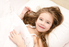 Adorable smiling little girl waked up. In her bed stock photo