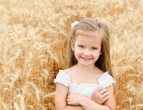 Adorable smiling little girl in the wheat field Royalty Free Stock Images