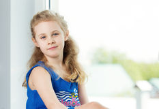 Adorable smiling little girl by the window stock photography