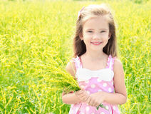 Adorable smiling little girl with yellow flowers on the meadow Royalty Free Stock Photos