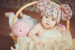 Adorable smiling newborn baby girl lies in basket Stock Photo