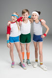 Adorable smiling sporty kids in sportswear standing together on grey. Children sport concept royalty free stock photography