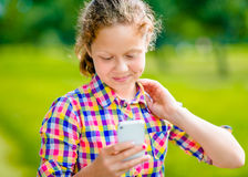 Adorable smiling teenage girl in casual clothes with smartphone. In her hand, looking at screen, reading a message, using Facebook in sunny day in summer park royalty free stock images
