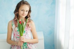Adorable smiling teenager girl with tulips. Copyspace Stock Photo