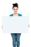 Adorable smiling teenager holding big ad board Royalty Free Stock Images