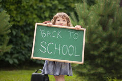 Adorable smiling toddler girl with back to school text blackboar. Cute caucasian little girl holding chalkboard written back to school. with a smile. ready and Royalty Free Stock Photos