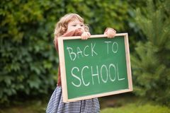 Adorable smiling toddler girl with back to school text blackboard. royalty free stock image