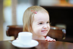 Adorable smiling toddler girl at cafe Stock Photo