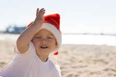 Adorable smiling toddler ina Christmas red hat playing on the beach Stock Photo