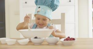 Adorable smiling toddler at mixing bowl Royalty Free Stock Photos