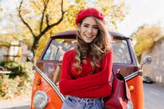 Adorable smiling woman in beret standing with arms crossed in front of orange bus. Outdoor portrait of joyful curly girl