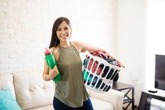 Young smiling woman holding laundry basket and detergent. Adorable and smiling woman standing with clothes in basket and holding washing soap bottle Royalty Free Stock Photos