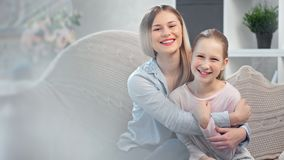 Adorable smiling young mother hugging cute daughter posing together surrounded by light glare. Medium shot. Happy family feeling love tenderness and positive stock video