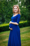 Adorable smiling young pregnant woman in blue dress with long blond curly hair holding her belly in summer park on rainy day Royalty Free Stock Images